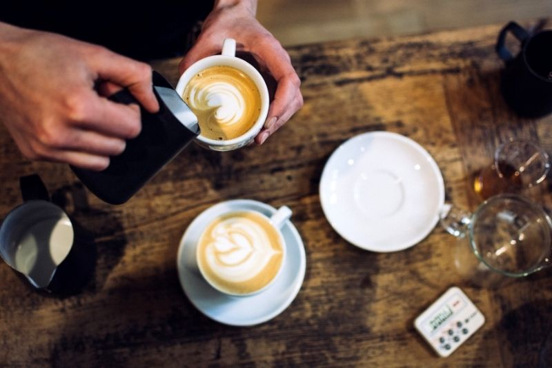 flatlay of man pouring milk into latte, How much does it cost to live in Portland Oregon pins (2)